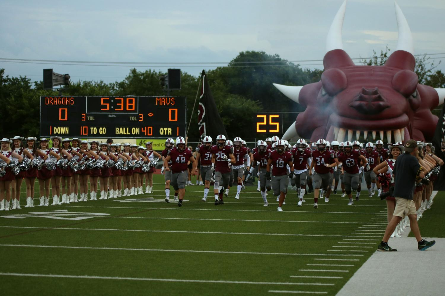 The Dragons run onto the field prior to their home and district opener.