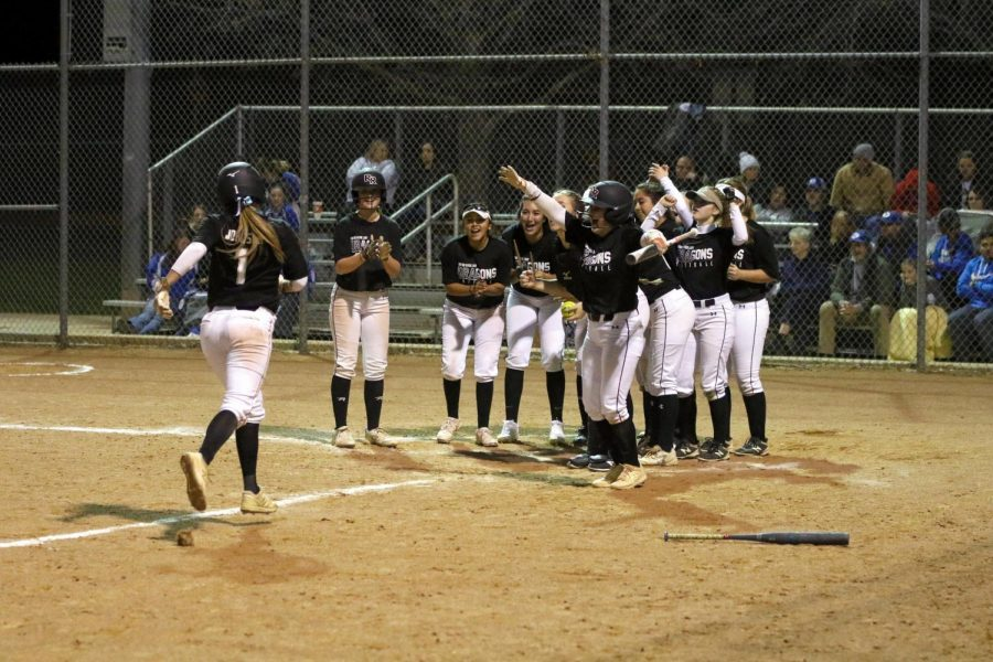 Dragon softball players round home plate as Madi Johnson arrives after a home run bomb